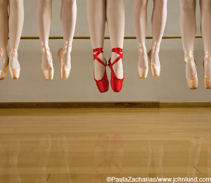 Close up picture of just the feet and slippers of a group of ballet dancers. The dancers have lept into the air so that all of their feet are in mid-air and toes are pointed down towards the hardwood dance floor.